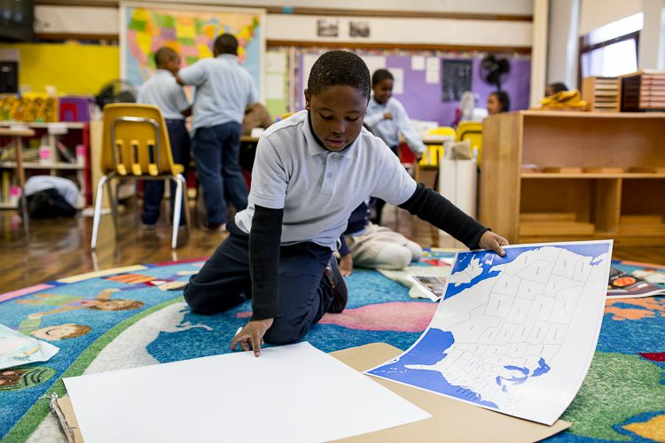 Detroit Montessori student Bryan Smith, 8, demonstrates how traced a classroom map to create his own, colorful map of the United States.