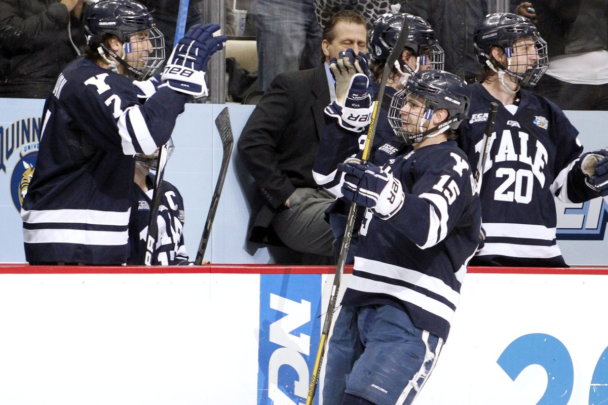 Keith Allain (background) on the bench as Yale celebrates with Clinton Bourbonais (15).