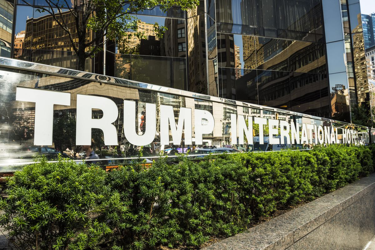 """A sign that reads """"Trump International Hotel and Tower"""" in large white letters."""