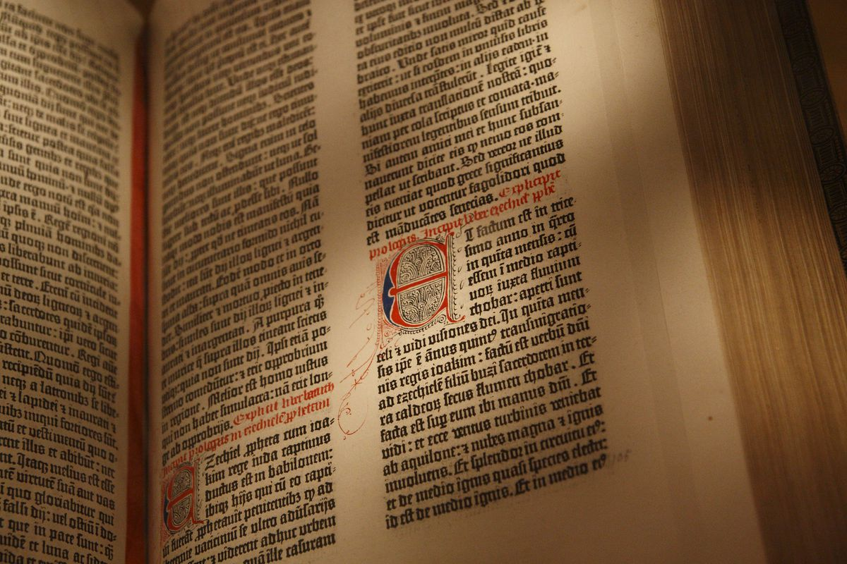"""Detail of a page from the Gutenberg Bible, showing a large illustrated letter """"E"""" styled next to the main text"""