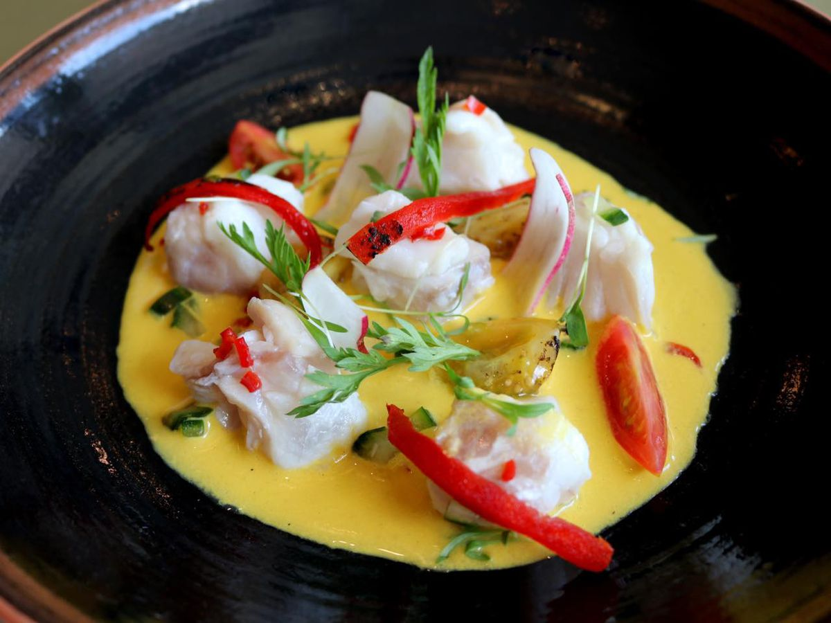 red snapper ceviche topped with red chiles on a black plate