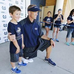 Utah State University football coach Matt Wells poses for a photo with his son Wyatt during a kids football camp in Logan Friday, June 12, 2015.