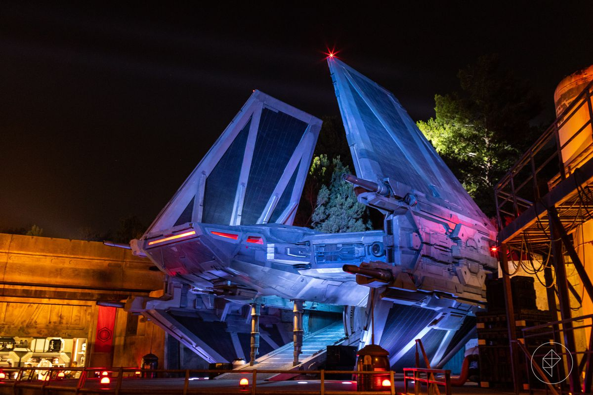 A spaceship illuminated with colorful light near buildings at Galaxy's Edge in Disneyland.