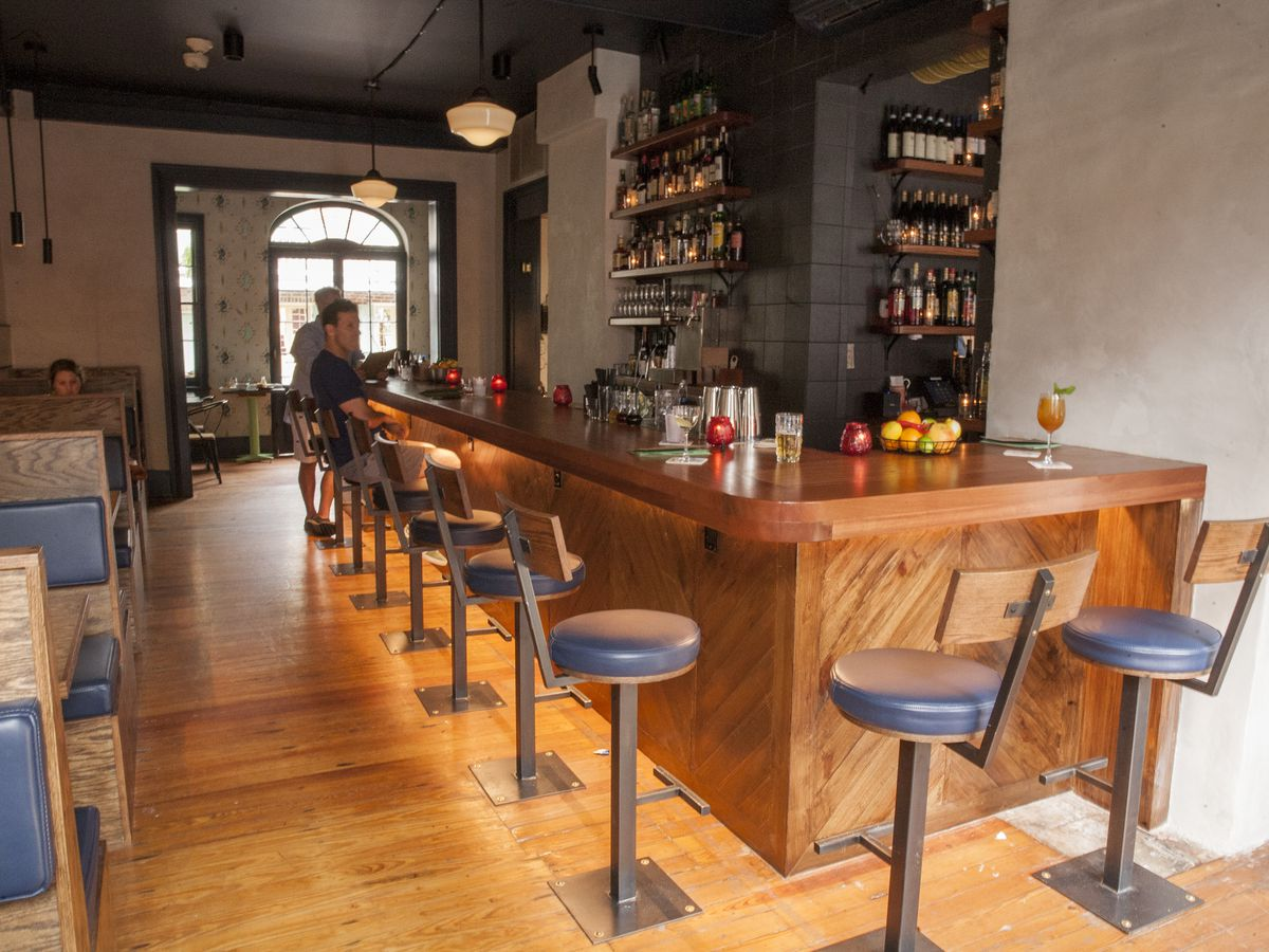 A wood bar on the right is lined with blue-topped stools; a column of four booth lines the left wall