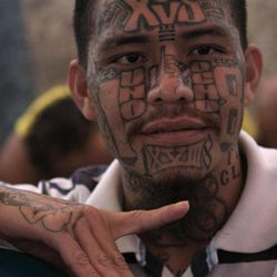 In this Sept. 1, 2012 photo, an inmate belonging to the Mara 18 gang gestures inside the prison in Cojutepeque, El Salvador. Six months after El Salvador brokered an historic truce between two rival gangs to curb the nation's daunting homicide rate, officials are split over whether the truce actually works. The gangs, which also operate in Guatemala and Honduras, are seeking truce talks in those countries as well.