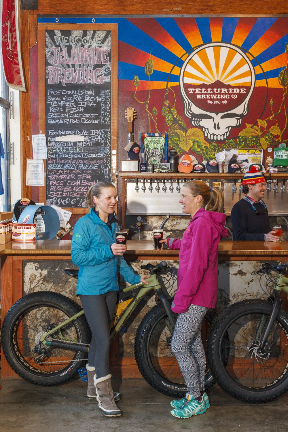 Two women having a drink at the bar at the Telluride Brewing Company, with a colorful mural of a skull head on the wall behind the bar.