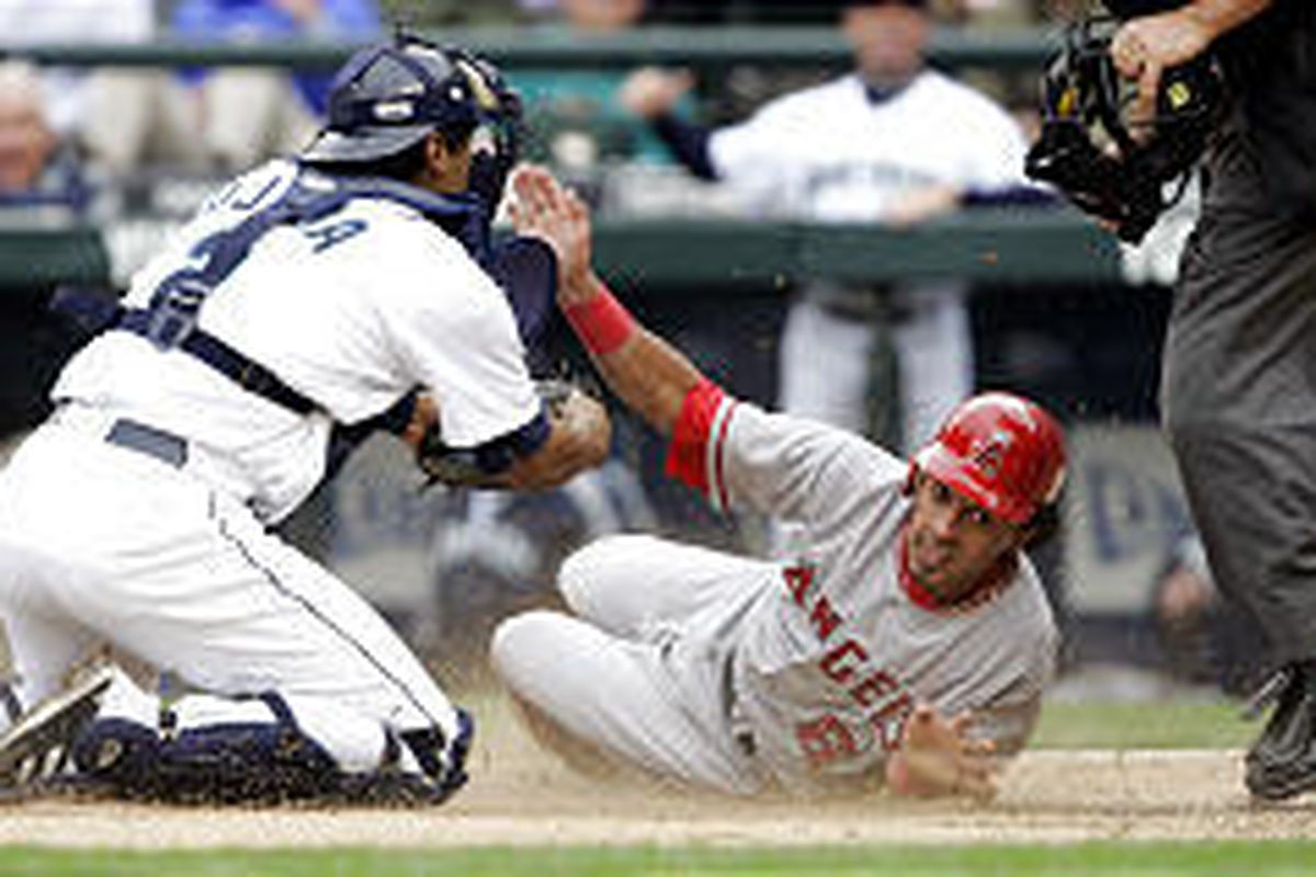 Angels' Maicer Izturis, right, looks up for the call after being tagged at the plate by Seattle Mariners catcher Miguel Ojeda in ninth inning Wednesday.