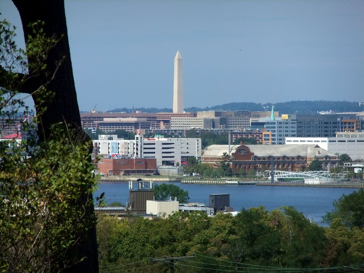 In the foreground are trees and a body of water. In the distance is the Frederick Douglass National Historic Site.