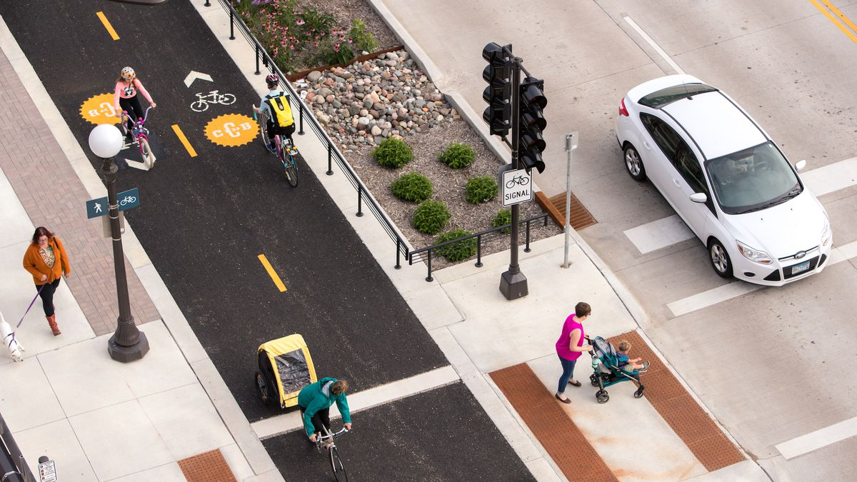 An aerial photograph of a street showing people walking, riding bikes, and driving.