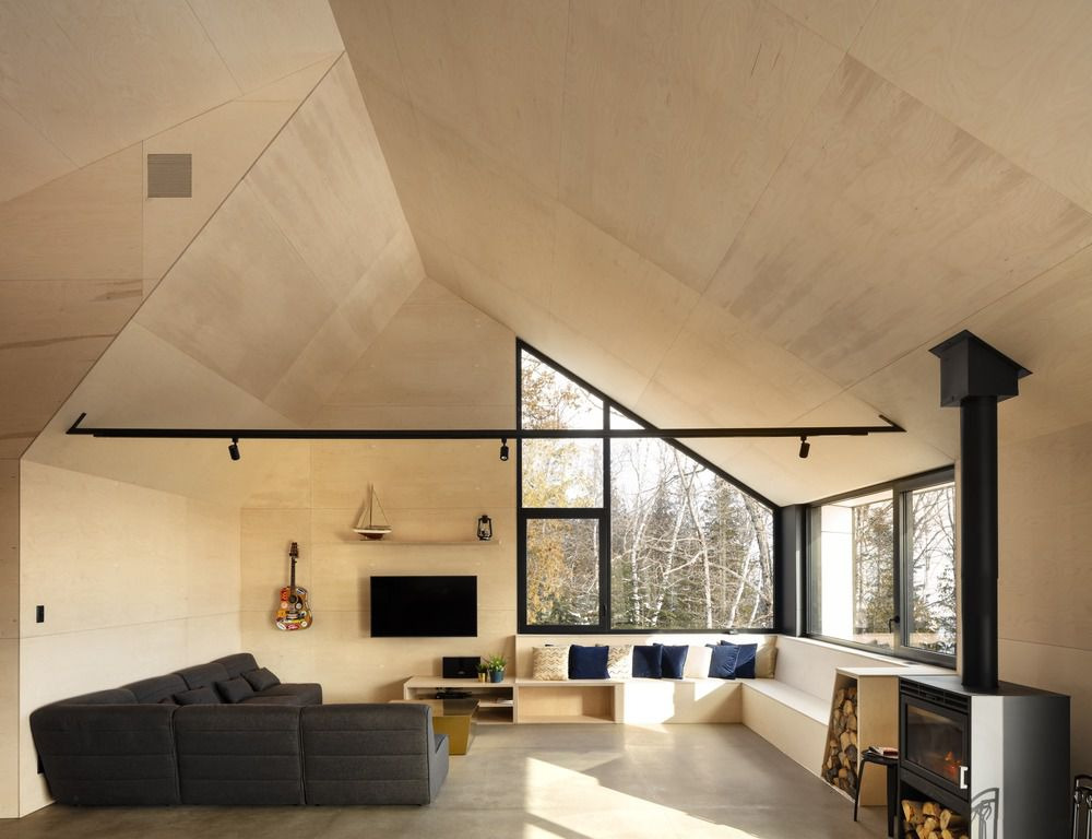 Living room clad in plywood with angular windows and a charcoal sectional sofa.