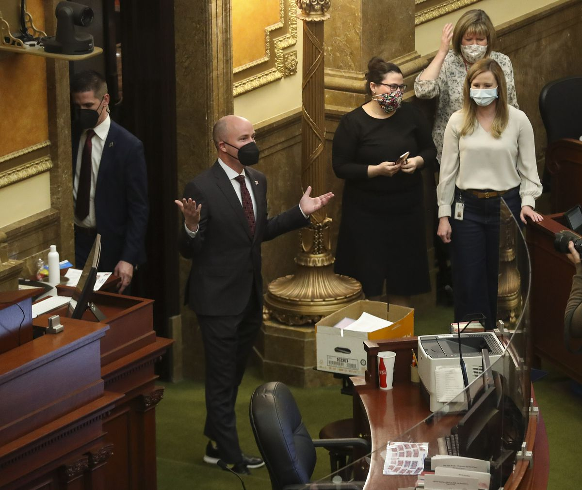 Gov. Spencer Cox, center, throws his hands in the air as he enters the House chamber after jokingly being introduced as Gov. Gary Herbert by Rep. Francis Gibson, R-Mapleton, at the end of the 2021 legislative session in the House chamber at the Capitol in Salt Lake City on Friday, March 5, 2021.