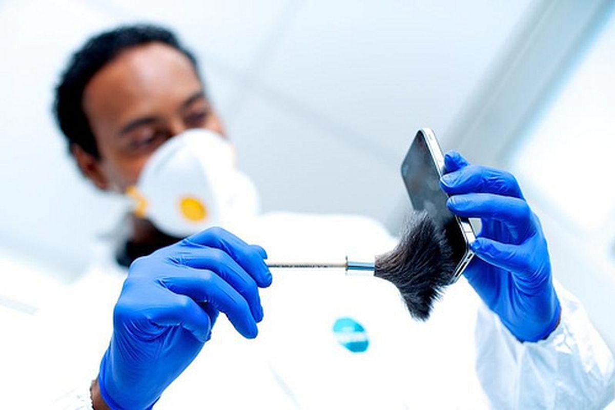 A lab technician dusts crime scene evidence.