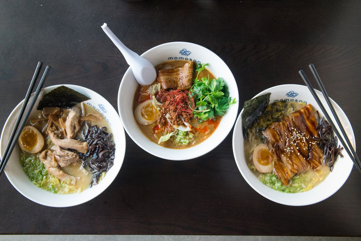A bird's eye view of three bowls of ramen soup, with chopsticks and a spoon laying on top. From left to right: Tokyo chicken soup, spicy tan-tan, and tonkatsu ramen.