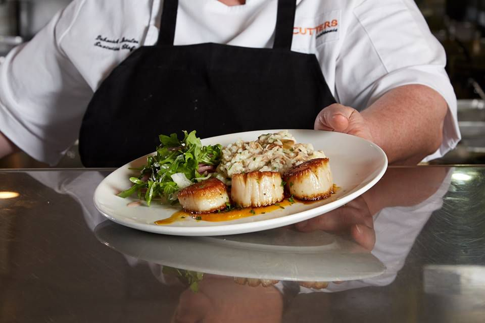 A chef holds a white plate with seared scallops, greens, and a starchy side.