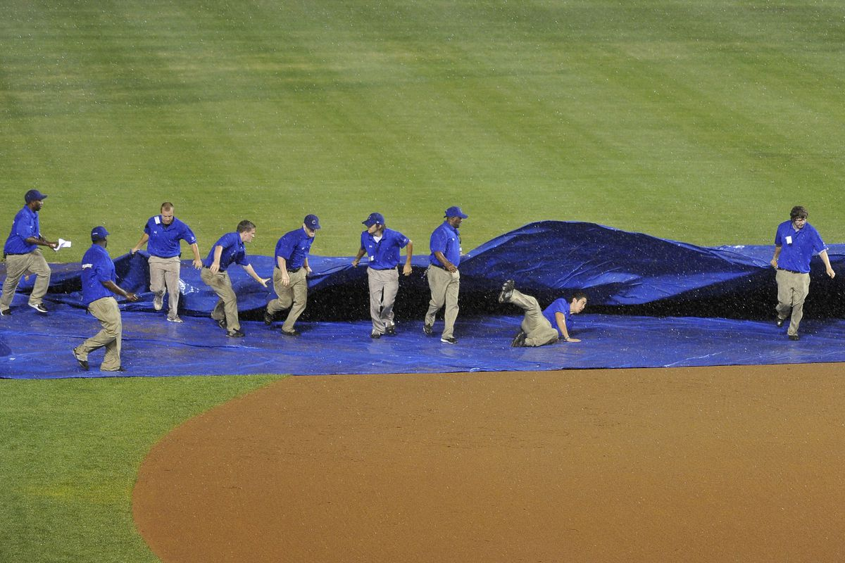 A member of the Chicago Cubs grounds crew falls as they unfold the tarp after play was suspended during the eighth inning Wednesday against the Miami Marlins at Wrigley Field in Chicago, Illinois.  (Photo by Brian Kersey/Getty Images)