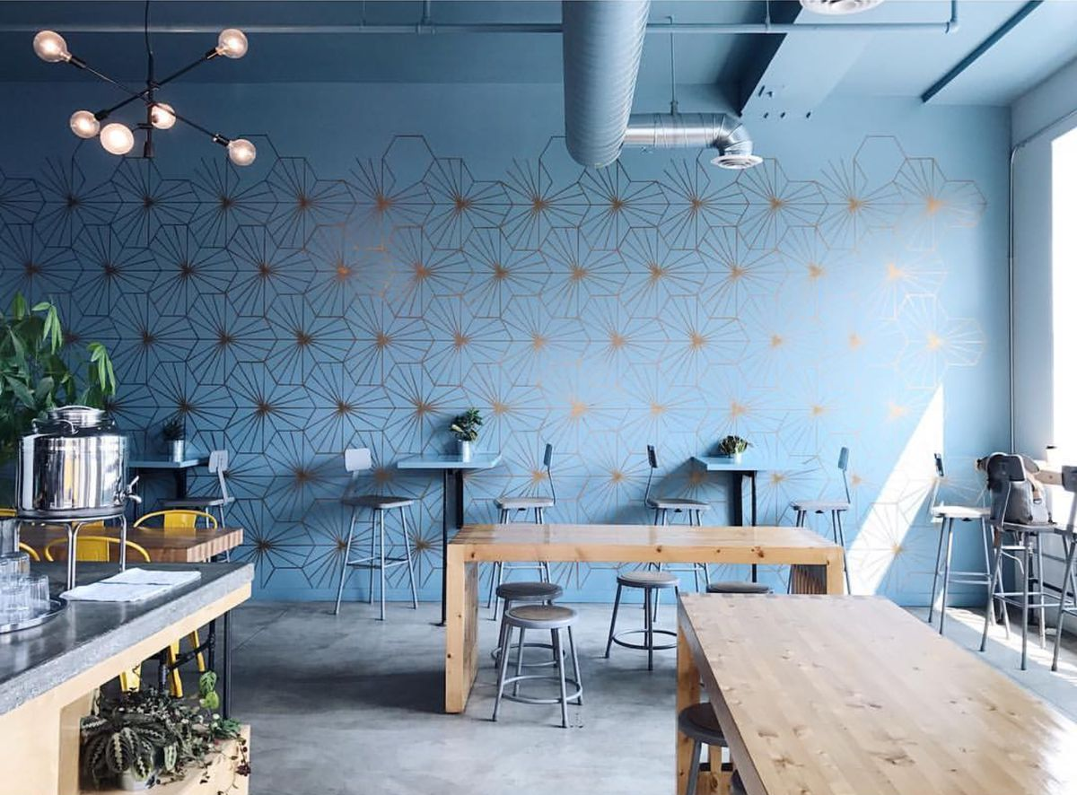 A view of a light blue wall and wood communal tables at Preserve and Gather.