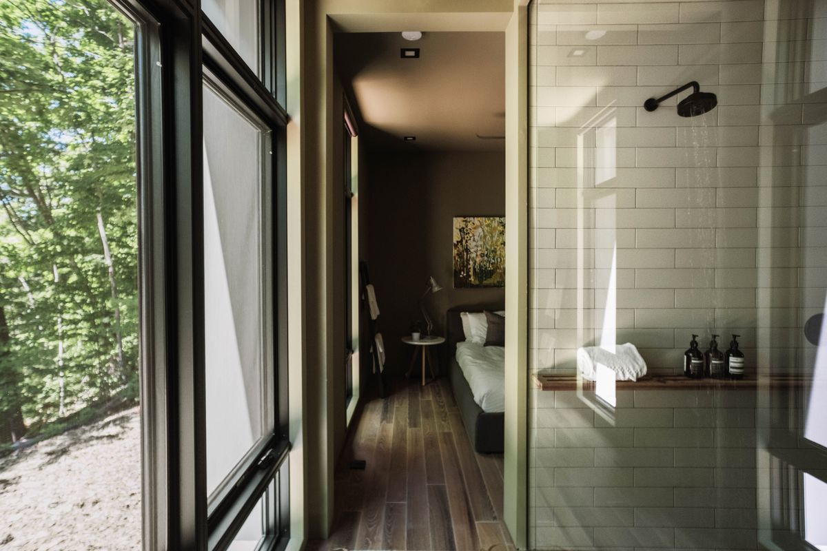 Corridor with a glass shower and view into the bedroom.
