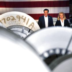 Mitt Romney and his wife Ann walk past rolls of sheet metal in the bellwether state of Ohio.