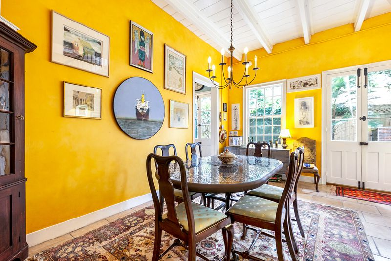 Yellow dining room with a six-person table, exposed ceiling beams, tile floors and an Oriental rug