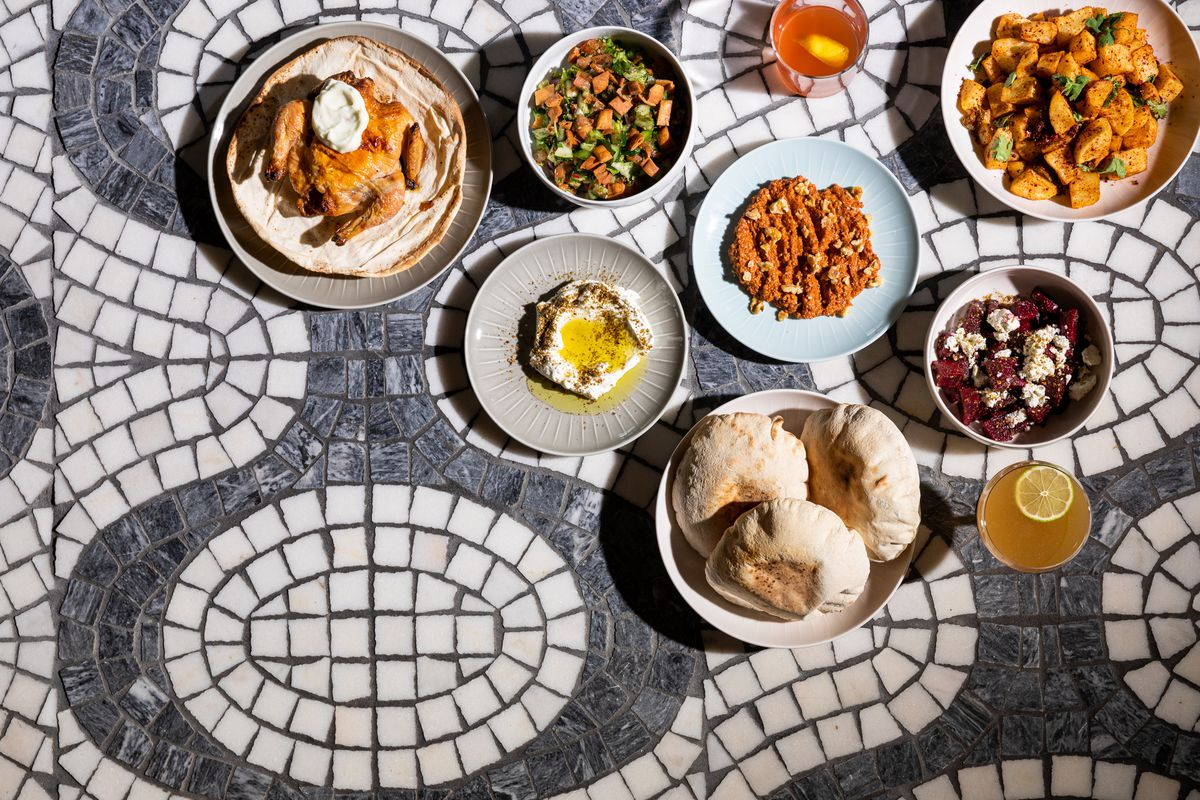 Plates of mezze scattered across a white and gray floor tiled in an intricate pattern.