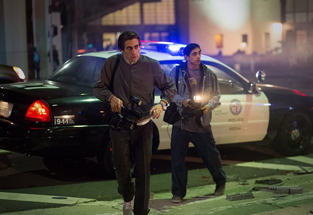 Freelance cameraman Lou Bloom (Jake Gyllenhaal) and his assistant Rick (Riz Ahmed) filming the scene of a car crash in Nightcrawler.
