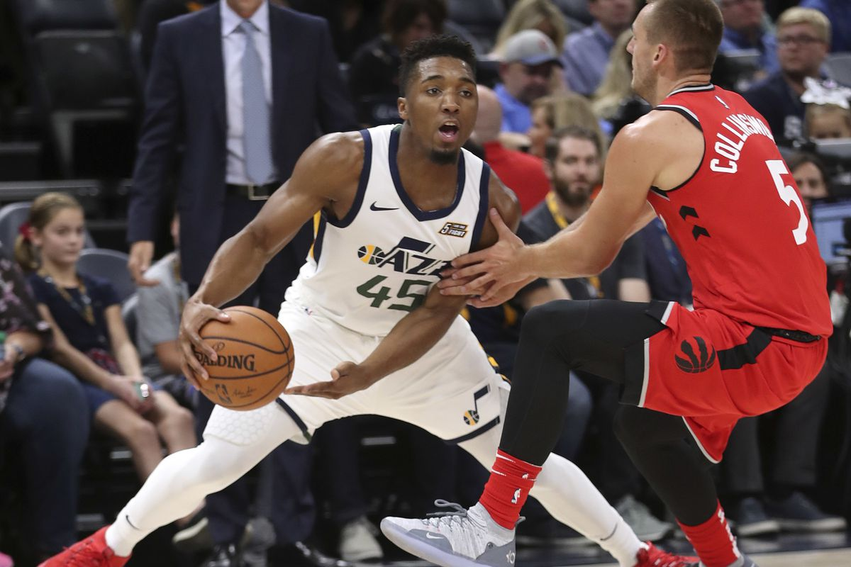 Toronto Raptors guard Kyle Collinsworth (5) tries to stay in front off Utah Jazz guard Donovan Mitchell (45) during the Toronto Raptors versus Utah Jazz preseason NBA basketball game at Vivint Arena in Salt Lake City on Tuesday, Oct. 2, 2018.