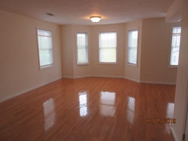 An empty living room with a bay window.