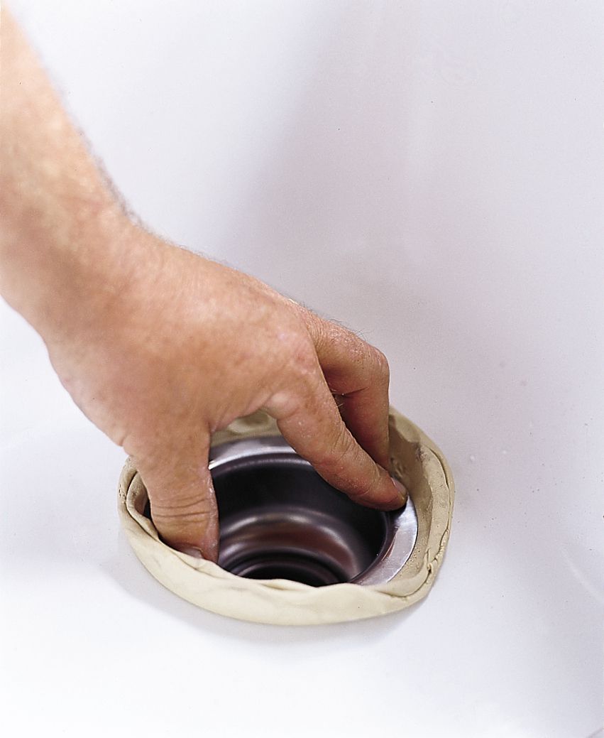 Person pressing down on a sink strainer over plumber's putty.