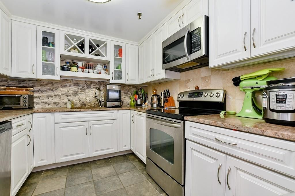 A small kitchen with a U-shaped counter and cabinetry above it.