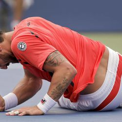 Janko Tipsarevic of Serbia lays on the court after slipping while playing Spain's David Ferrer in the quarterfinals during the 2012 US Open tennis tournament,  Thursday, Sept. 6, 2012, in New York.