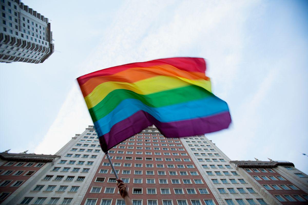 A demonstrator waves an LGBT Pride flag in Spain.