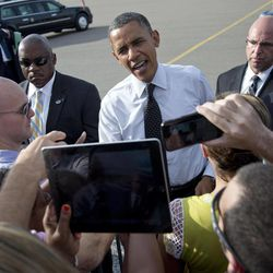 President Barack Obama greets people on the tarmac as he arrives at Tampa International Airport on Air Force One, Thursday, Sept. 20, 2012, in Tampa.