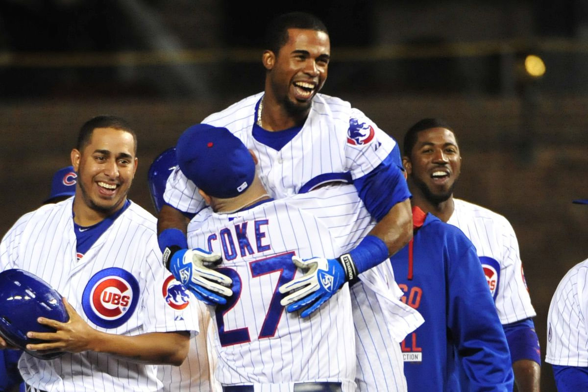 Two men who didn't last long with this year's Cubs hug each other after a walkoff win
