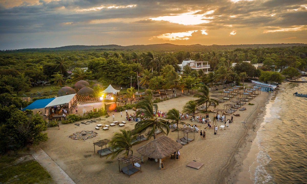 An aerial view of a beach at sunset, with trees stretching into the distance, huts and beds covering the beach, and people visiting below