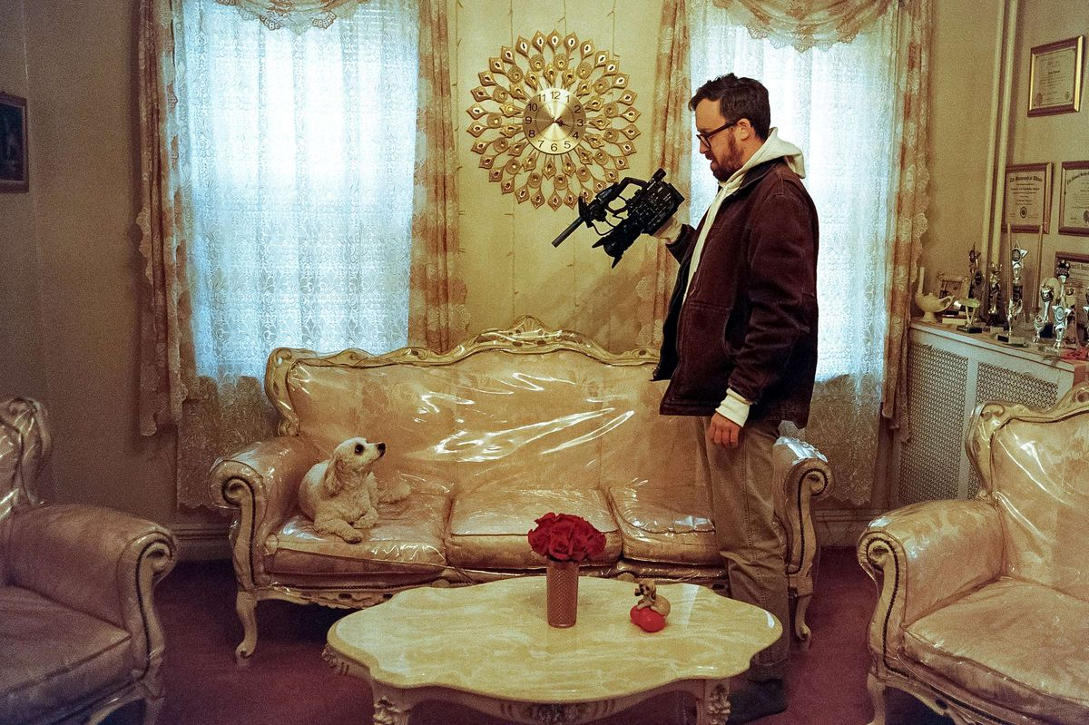John Wilson stands with a camera filming a dog sitting on nice furniture covered with plastic wrap