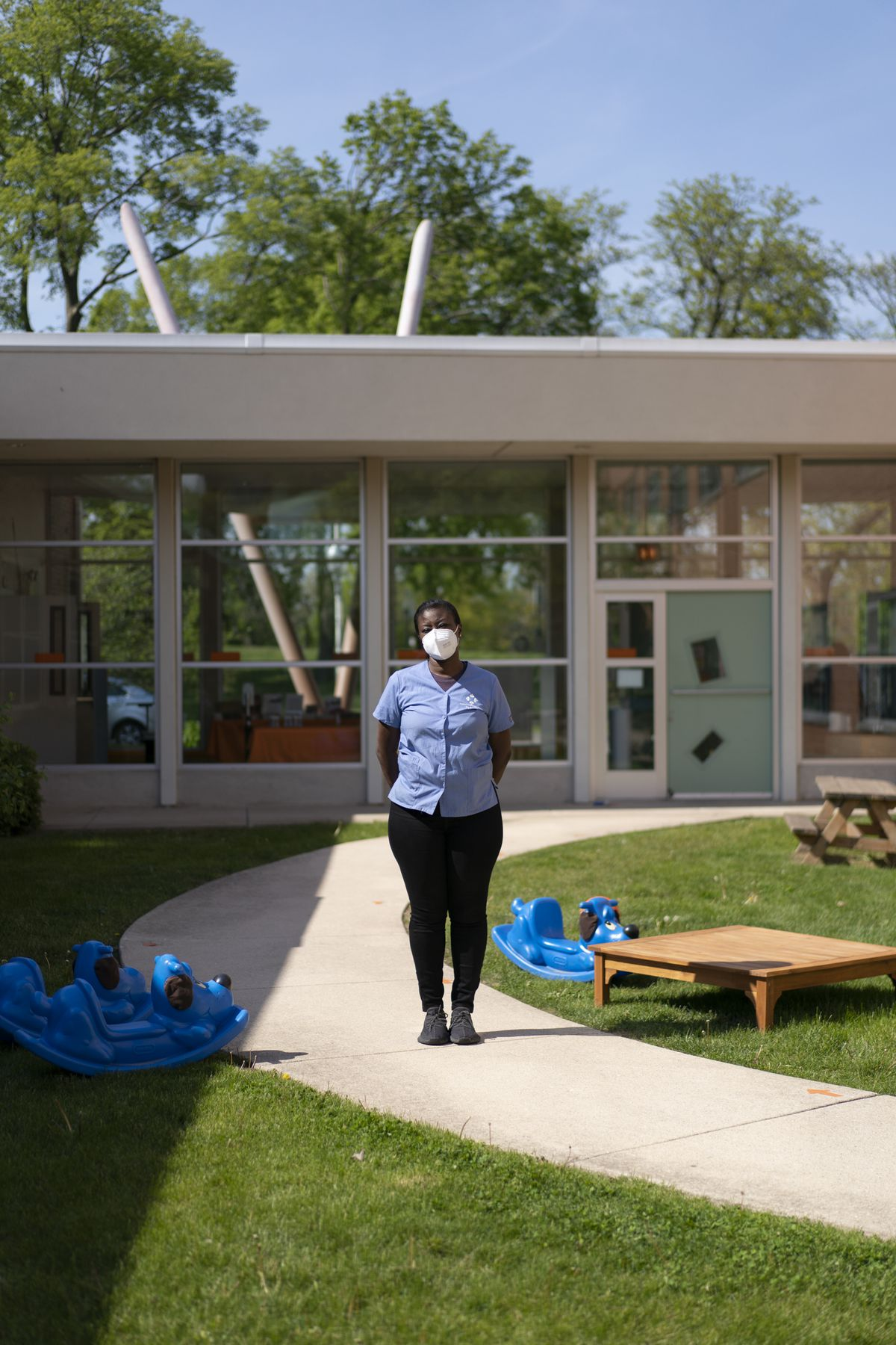 A woman wearing a blue shirt, black pants and a KN-95 mask stands for a portrait in front of a building with large glass windows. There are blue rocking toys and a wood table next to her on either side.
