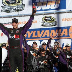 NASCAR driver Denny Hamlin celebrates with his team after winning the NASCAR Sprint Cup Series auto race at New Hampshire Motor Speedway, Sunday, Sept. 23, 2012, in Loudon, N.H.