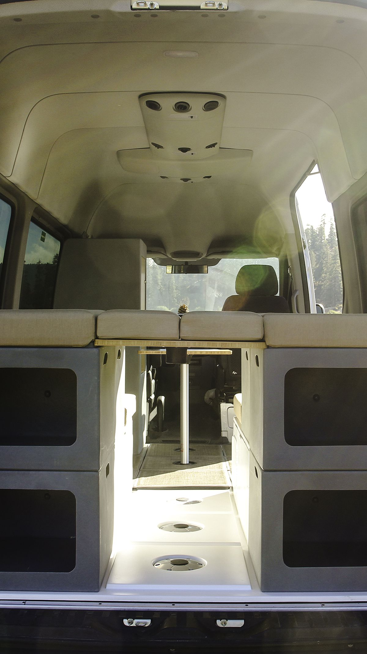 The inside of a camper van features four gray cubes with storage openings stacked together. On top of the cubes is a cushion that works as a bed.