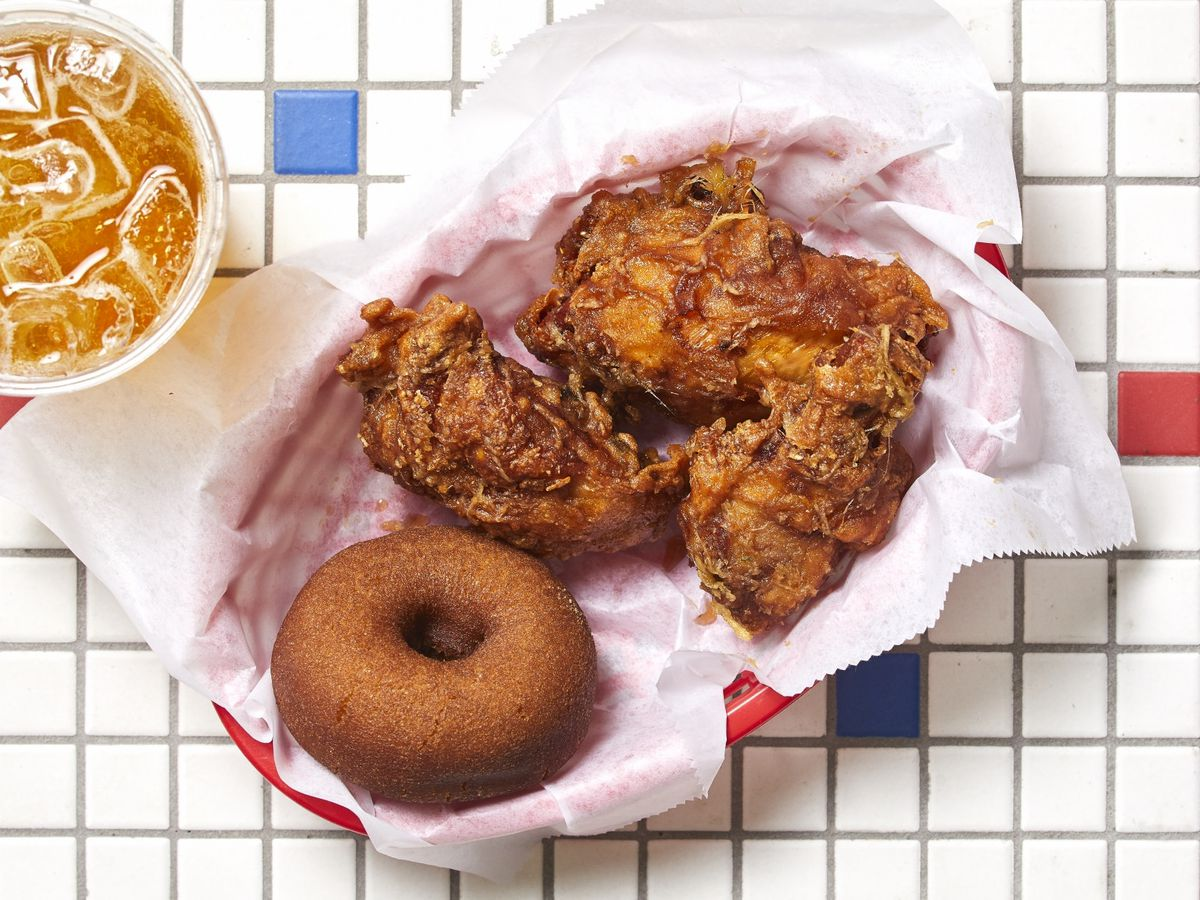 basket with fried chicken and doughnut next to an icy drink