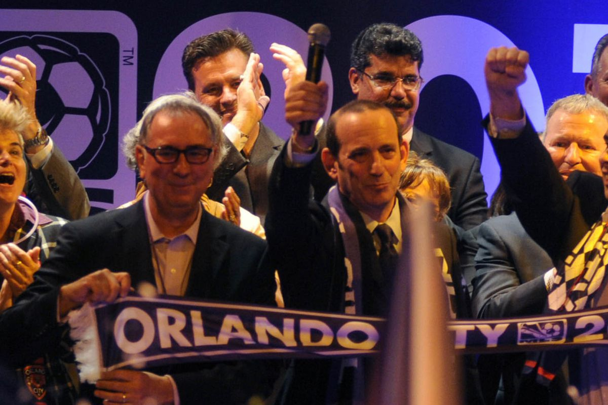 Rawlins (left) next to MLS Commissioner Don Garber.
