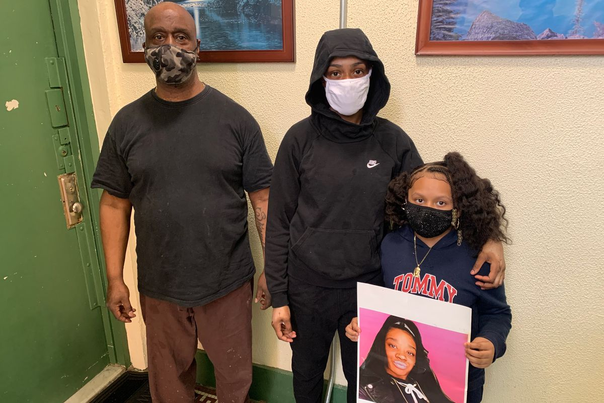 MTA worker Reginald Frazier and his daughters Shalae, 16, and Shaleah, 7 hold a photo of their sister, Shaimeek, who passed away in April of COVID-19.