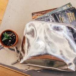 """""""Metallic accessories are a big trend for spring, and here are two perfect examples: a mirrored patent leather clutch from the Danish brand Wood Wood, and the super soft matte silver backpack from Collina Strada (below)"""". <b>Wood Wood</b> Tri Purse, $145"""