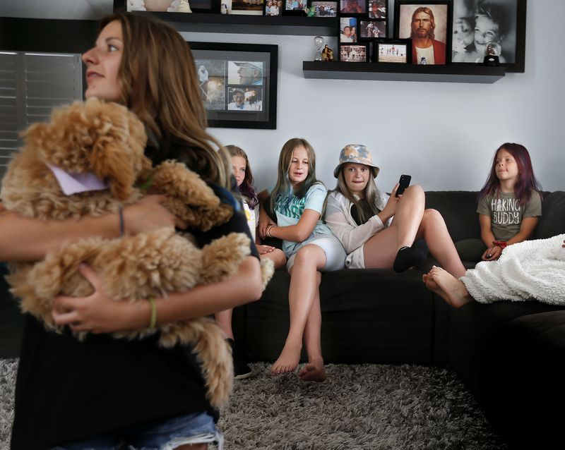 Marley Ethington holds the family puppy, Bella, as her cousins Lyla Leonhardt, Roxy Leonhardt, sister Ava Dolato, and cousin Quin Leonhardt, relax on the couch the morning after a sleepover at their Midvale home on Thursday, June 4, 2020.