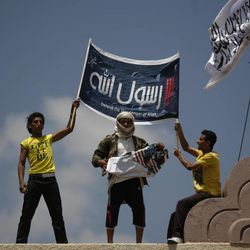"""A Yemeni protestor, center, destroys an American flag pulled down as other hold a banner in Arabic that reads, """"any one but you God's prophet"""" at the U.S. Embassy compound during a protest about a film ridiculing Islam's Prophet Muhammad, in Sanaa, Yemen, Thursday, Sept. 13, 2012. Dozens of protesters gather in front of the US Embassy in Sanaa to protest against the American film """"The Innocence of Muslims"""" deemed blasphemous and Islamophobic."""