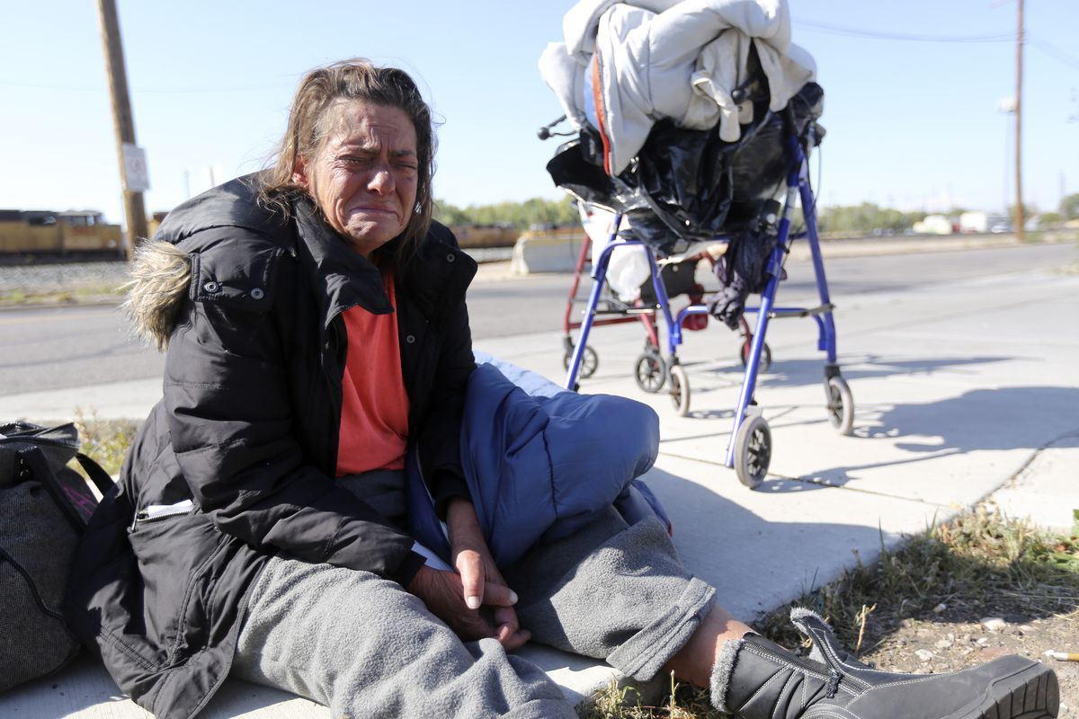 """Stacy Evans cries while sitting on a sidewalk outside of the Lantern House, a homeless shelter in Ogden, on Tuesday, Oct. 1, 2019. """"We've been through hell. It sucks to be homeless,"""" she says."""
