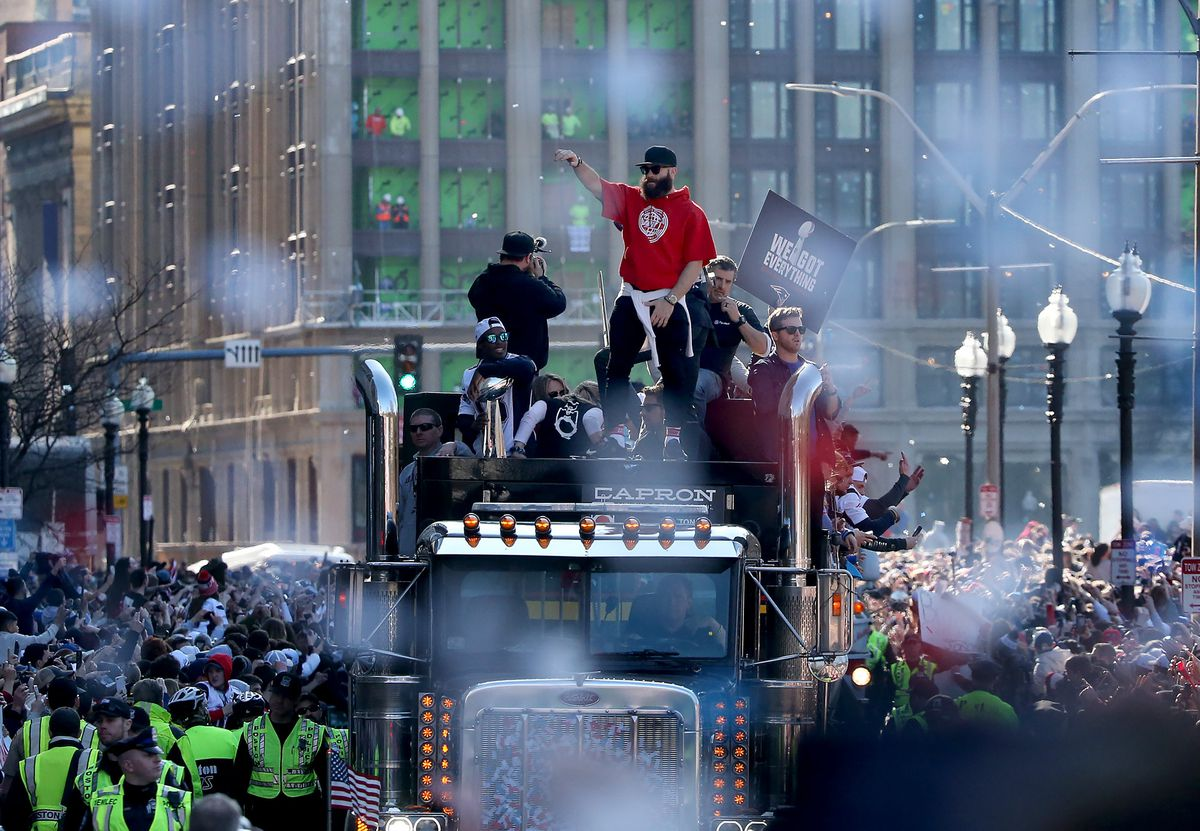 Men on a truck making their way through a cheering crowd in a downtown city.