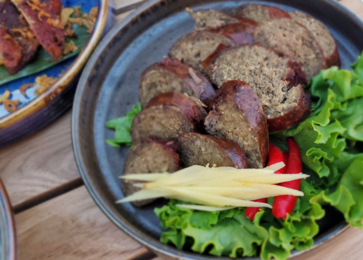 A plate of sausage cut into slices with a side salad and tomatoes