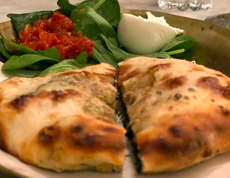 A spinach kulcha on a plate with burrata