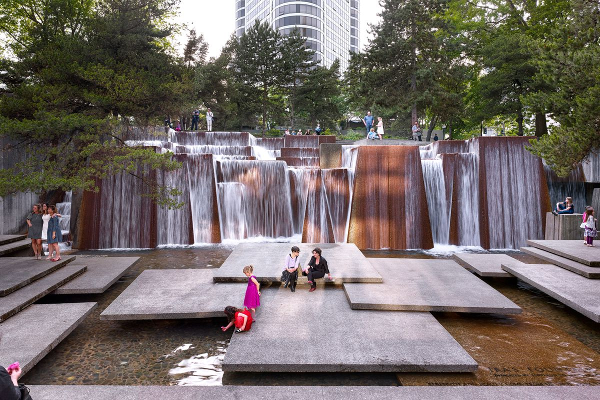 People mill about a series of squared concrete platforms hovering above water, which flows from a slanted waterfall in the background.