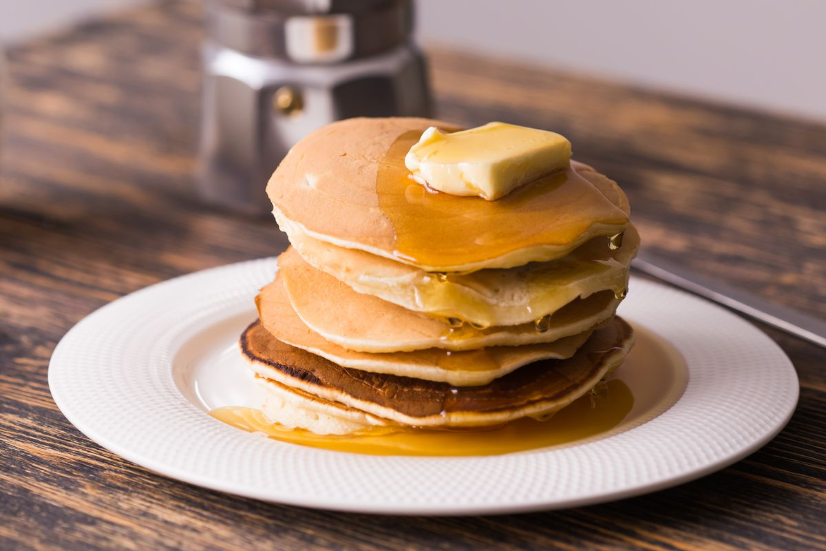 A stack of five fluffy pancakes on a plate with a pat of butter on top.